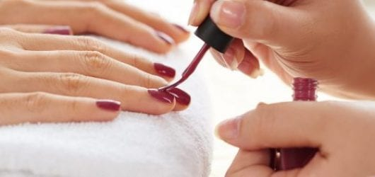 Image of Side view of manicurist applying nail polish