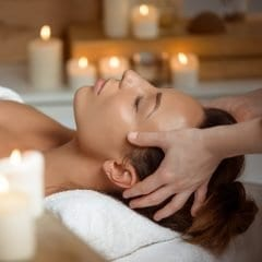 Image of a woman having a relaxing spa treatment surrounded by candles