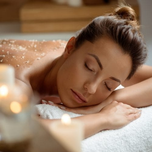 Image of a woman lying on her stomach with a body scrub on her back