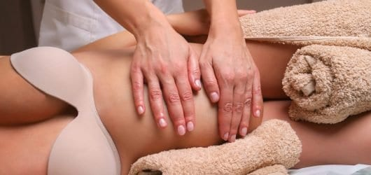 Image of Massage therapist massaging pregnant woman.