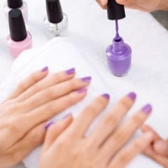 Image of Nail care: manicurist applying lacquer.
