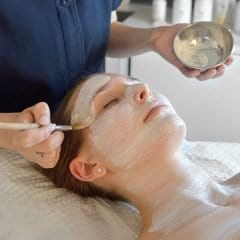 Image of a woman having a mask brushed on her face