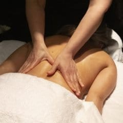 Image of Woman lying face down on a salon bed while a therapist massages her back.