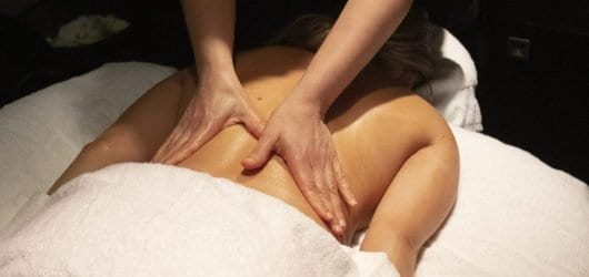 Woman lying face down on a salon bed while a therapist massages her back.