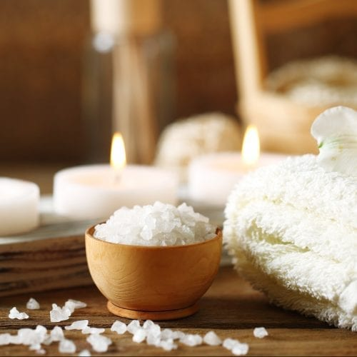 Image of Composition of spa treatment, candles in bowl with water on wooden background