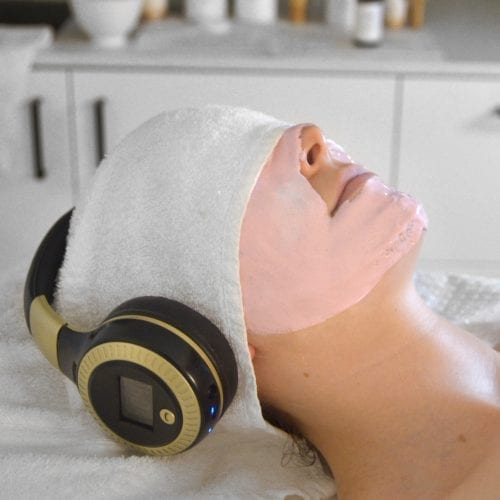 Young woman having a Ginger&Me Mindfulness Facial with headphones on