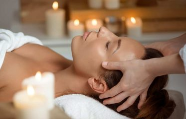 Young woman having face massage relaxing in spa salon. Eyes closed.