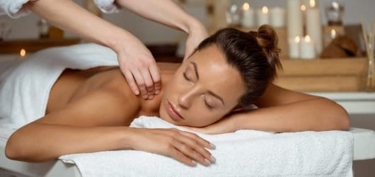 Young woman having massage relaxing in spa salon.