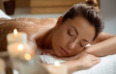Young woman relaxing in a spa salon with exfoliating scrub on her back.