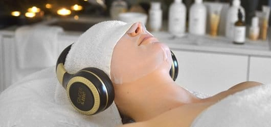 Young woman on a beauty spa bed with a towel and headphones over her head, enjoying a paper mask facial.