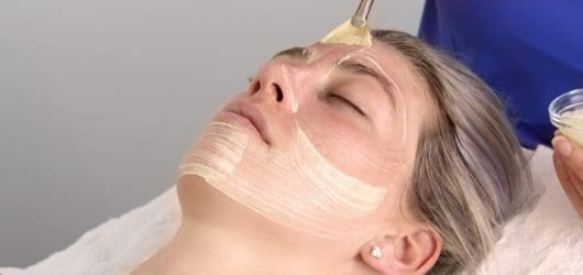 Young woman on a beauty spa bed, having a chemical peel brushed on to her skin by a therapist.