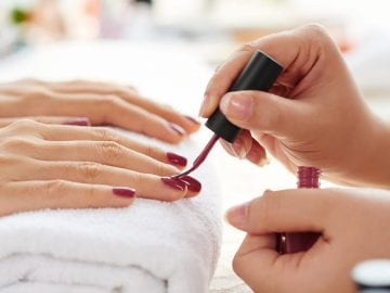 Image of Side view of manicurist applying nail lacquer.