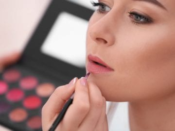 Image of a woman having makeup applied professionally