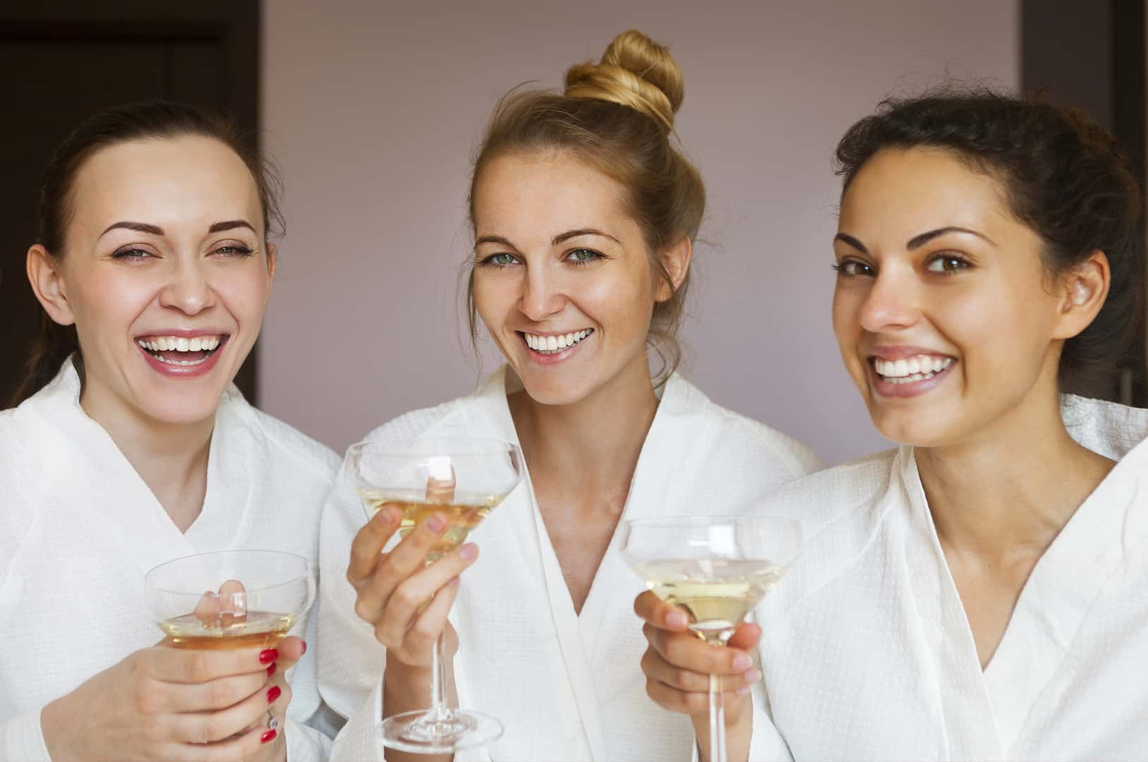 Image of three women in white robes, laughing and drinking champagne