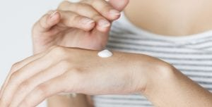 Banner Image of a woman putting cream on her hands