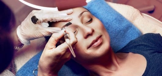 Beautician applying japanese method of drawing on eyebrows to model.