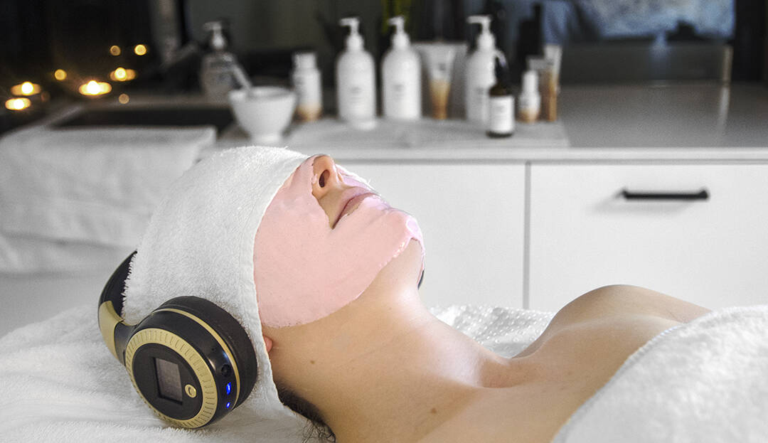 Image of Young woman on a salon bed with a pink alginate mask on her face, with headphones over her ears.