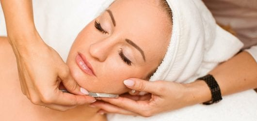 Image of a woman with her head wrapped in a towel, having a dermaplaning treatments