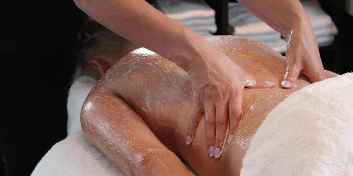 Young woman on a salon bed receiving a full body scrub by a beauty therapist.
