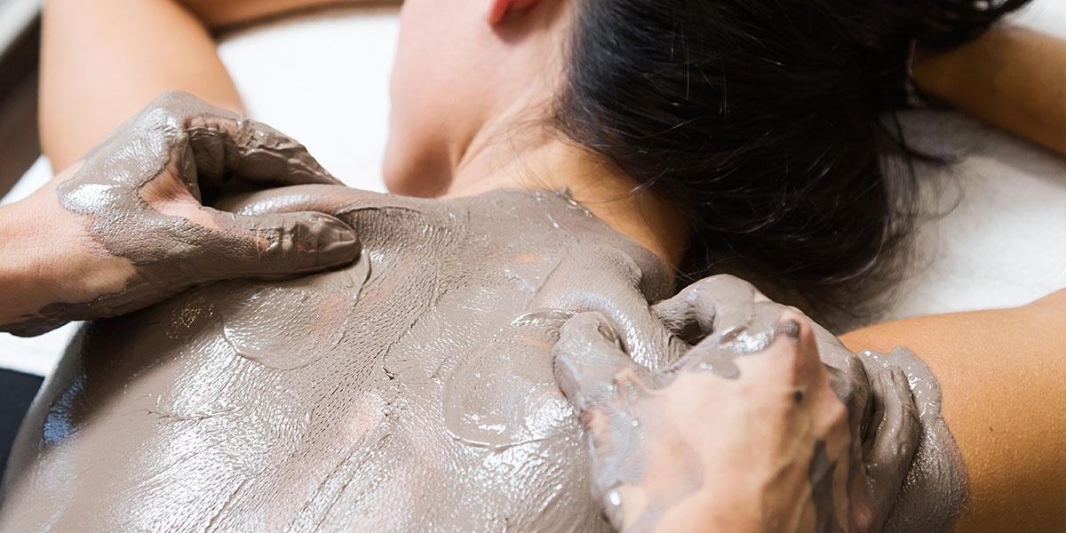 woman having a clay body mask treatment in christchurch nz